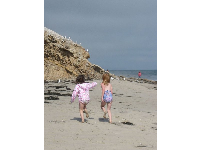 Girls running along the beach on a summer day.