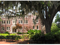 Brick building with cream trim, and oak tree with Spanish moss.