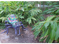 Spider sculpture in the bushes.