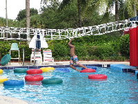 A boy tries his luck on the lily pad walk, a sort of monkey bar course above water!