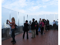 Visitors look through the glass at the lowest observation deck.